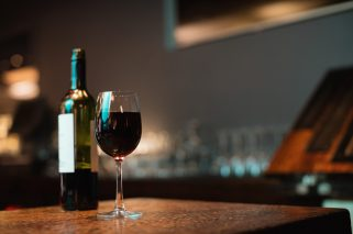Glass of red wine and bottle on bar counter at bar