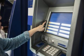 People waiting to get money from automated teller machine - people withdrawn money from ATM concept